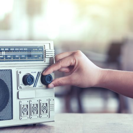 Woman hand adjusting the sound volume on retro radio cassette stereo  in vintage color tone